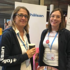två leende kvinnor med glasögon står vid en skylt med Folkhälsan. Den ena har en munktröja där det står Folkhälsan och en papperskaffekopp i handen
