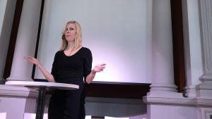 "Jessikka Aro talar vid sin bokpublicering, under väggtexten: ""Herran pelko on viisauden alku"""