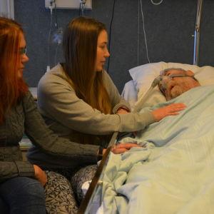 Carola Backholm (till vänster) och Tina Norrgrann hälsar på sin pappa Frank på Vasa centralsjukhus.