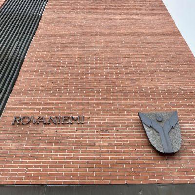 Tiiliseinä, jossa on kiinni Rovaniemi-sana sekä kaupungin vaakuna