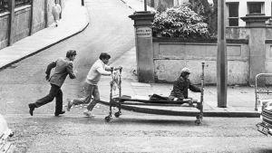 Kaksi miestä juoksee kadulla, toinen työntää sänkyä, jolla istuu kolmas mies.