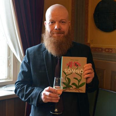 En man står inomhus vid ett fönster. Han ler och tittar mot kameran. I ena handen håller han ett glas med skumvin, i den andra en bok med namnet Sömnö.