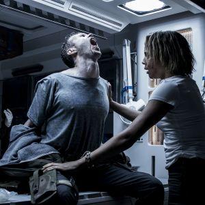 En blodig man sitter på ett operationsbord och har konvulsioner, två kvinnor försöker hjälpa honom.