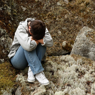 Ung person med huvudet nerböjt i vacker naturmiljö.