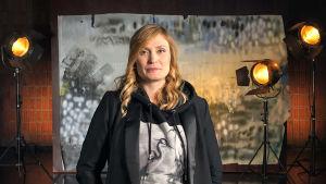 Miia Tervo seisoo studiossa taustalavasteen ja studiolamppujen edessä. Kuva otettu lyhytvideosarjaan Me elokuvantekijät.