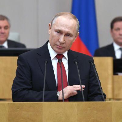 Rysslands president Vladimir Putin står vid ett talarpodium.
