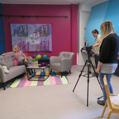 Kårkullas tv-studio. Två personer filmar en tredje person som sitter i en soffa i ett färggrant rum.