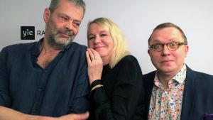 Radiotoimittaja Roman Schatz, näyttelijä Miitta Sorvali ja koomikko-kirjailija Antto Terras poseeraavat Yle Radio 1:n taustalakanan edessä.