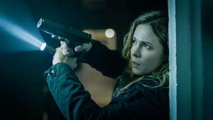 Sofia Karppi pitelee käsissään asetta ja taskulamppua ja osoittaa niitä uhkaavan näköisessä tilanteessa ylöspäin.