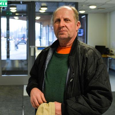 En medelålders man står i en aula i en hälsostation.