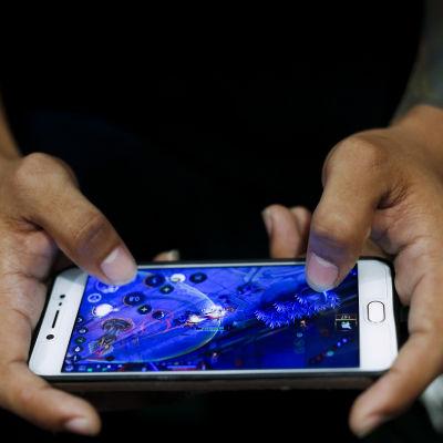 En person spelar ett mobilspel.