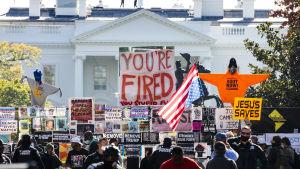 """Massa protestskyltar utanför Vita huset. På den största som syns på bilden står: you are fired, alltså """" du har fått sparken""""."""