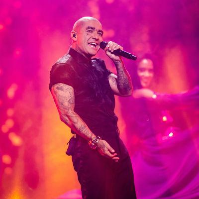 Tatuerad man i svarta kläder sjunger i en mikrofon