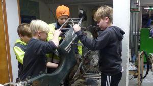 Fyra pojkar i ålder 10-12 skruvar isär en gammal moped. De är inne i en verkstad.
