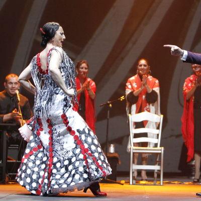 Flamencoesitys, jossa naistanssija ja laulaja Miguel Poveda sekä taustalla kitaristi ja palmas.