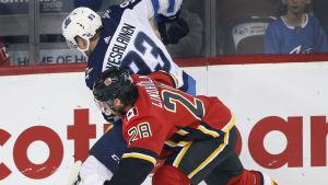 Winnipegs Kristian Vesalainen i en duell mot Calgarys Elias Lindholm.