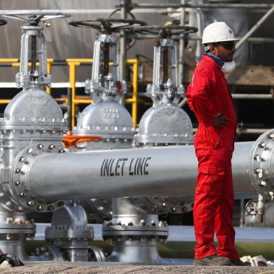 Haalaripukuinen työntekijä seisoo öljyputken vieressä