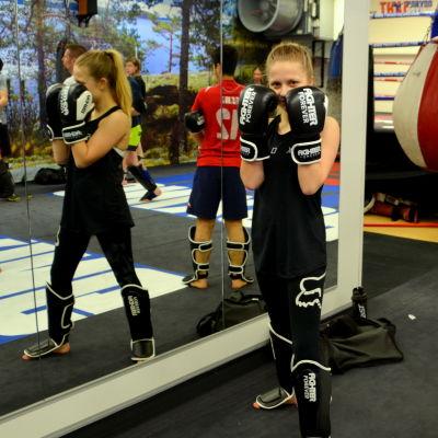 En kvinna står med boxningshandskarna framför ansiktet framför en spegel.