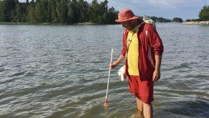Tobias Lillqvist mäter temperaturen i strandvattnet.