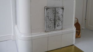 en del av en gammal vit kakelugn på Villa Snäcksund. Silverfärgade ugnsluckor.
