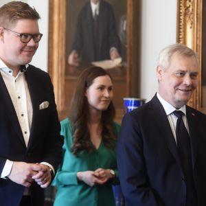 Från vänster Antti Lindtman, Sanna Marin och Antti Rinne. De står på rad i bakgrunden syns tavlor med guldram