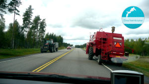 En tröska och en traktor stoppar upp trafiken i båda filerna på den asfalterade vägen som omges av skog. Uppe i högra hörnet finns en stämpel där det står Dina hemknutar.