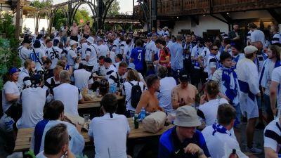 Finländska fotbollsfans i S:t Petersburg. De står på en innergård klädda i finländska tröjor och väntar på att en match ska börja.