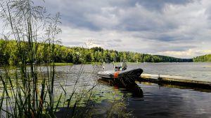 En båt ligger förtöjd vid en brygga.