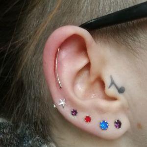 Tatuering som föreställer en not, tatuerad intill örat.