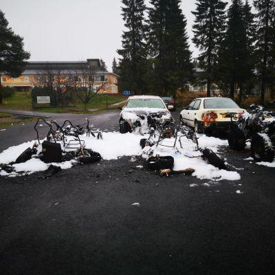 Kuvassa palaneita ja vaurioituneita autoja Keminmaan kirjaston parkkipaikalla.
