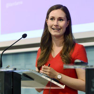 Sanna Marin i en röd tröja ståendes vid en talarstol.