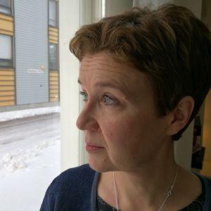 Författaren Sirpa Kähkönen ser ut genom ett fönster i närheten av sitt hem i Wiik. 2017.