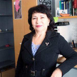 Professori Valentina Teosa istuu työpöytänsä ääressä