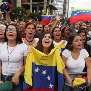 Demonstranter lyfter händerna i luften när Guaidó utnämner sig själv till president.