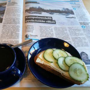 Kahvikuppi ja juusto-kurkkuvoileipä, siniset Teema-astiat sanomalehdellä