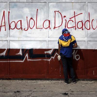 """En demonstrant håller i stenar i sammandrabbning med polis i Venezuela. På väggen står """"Ner med diktaturen"""" på spanska."""
