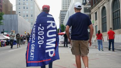 En Trumpsupporter inlindad i en kampanjfana promenerar på gatan i Tulsa i Oklahoma.