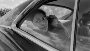 Cleo (Yalitza Aparicio) sitter i baksätet i en bil och ser ut genom fönstret.