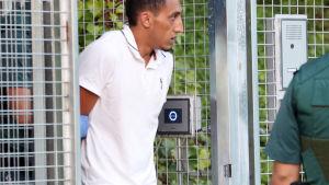 Driss Oukabir som misstänks vara medlem i terrorcellen bakom Barcelonaangreppet leds till rätten av poliser.