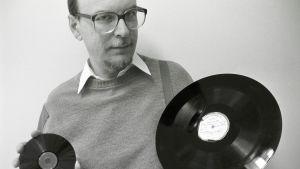 Pekka Gronow kädessään cd-levy ja pikatallenuslevy