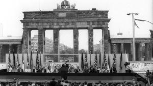 USA:s president Ronald Reagan talar vid Berlinmuren framför Brandenburger Tor.