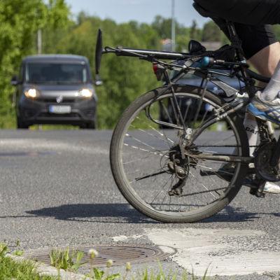 Anonyymi pyöräilijä ylittämässä suojatietä