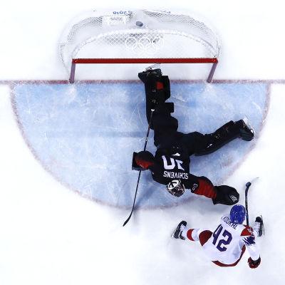 Ishockeymålvakten Ben Scrivens ligger på mage för att få tag i pucken.