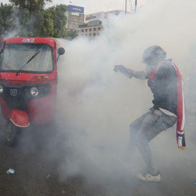 En demonstrant i ett moln av tårgas i Bagdad