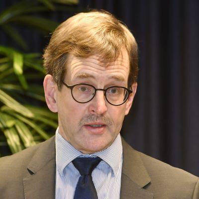 En man i brun kostym, ljusblå skjorta och mörkblå kravatt, med glasögon och kort brunt hår och mustasch tittar in i kameran. I bakgrunden en mörk gardin och en krukväxt.