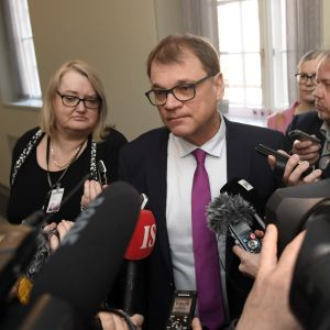 Juha Sipilä omringad av kameror och journalister i riksdagen.