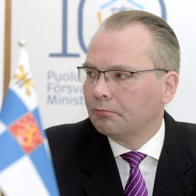 Porträtt på försvarsminister Jussi Niinistö vid en standard med finska flaggan.