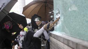 Demonstrant krossar ett skyltfönster i Hongkong.