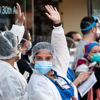 Sjukvårdspersonal utanför Mont Sinai-sjukhuset i Queens, New York, reagerar på hyllningar från stadens invånare.