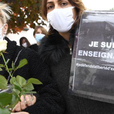 """Två kvinnor håller i en skylt med texten """"Jag är lärare""""."""